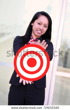 A pretty asian business woman holding target at office