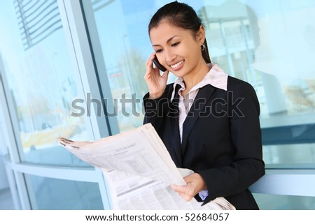 A pretty asian business woman on the phone at office building