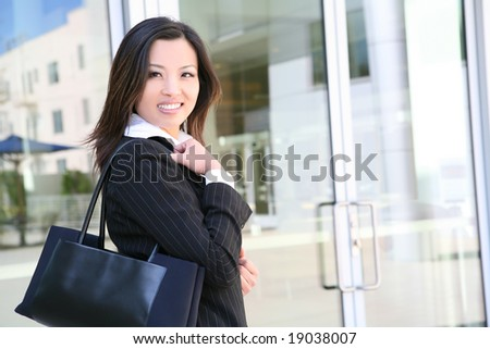 A pretty asian business woman outside office building