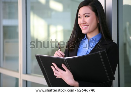 A pretty asian business woman with notebook at office building