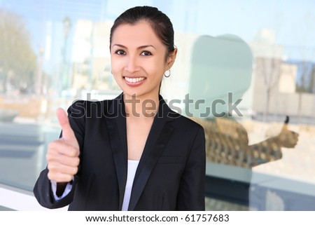 A pretty asian business woman with thumbs up celebrating success