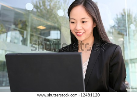 A pretty asian business woman working on the laptop