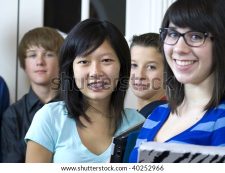 A pretty Asian girl with a group of her fellow schoolmates, stop and smile big for the camera.