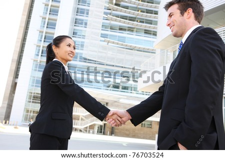 A pretty asian woman handshake with handsome man at office building