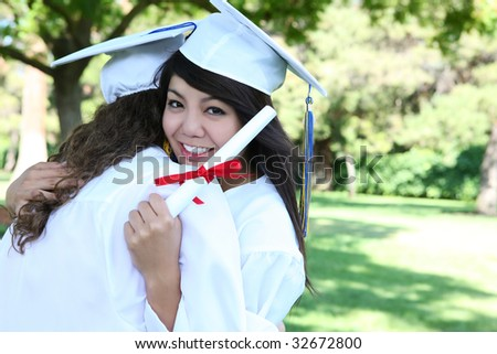 A pretty asian woman hugging a friend and holding her diploma at graduation
