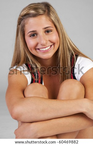a pretty blond young teen girl sitting and smiling.