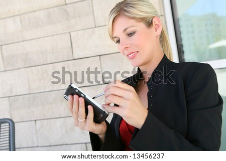A pretty blonde business woman working on pda at office building