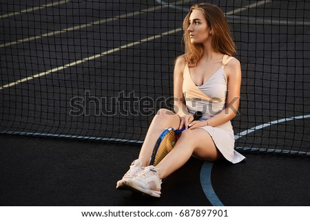 A pretty blonde is tired of a grueling tennis game.Sexy young brunette woman siting on a tennis clay court on sunny day. beautiful young woman in sports clothing holding tennis racket.
