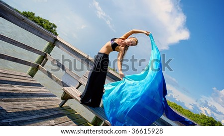 a pretty blonde woman looking at viewer with her arms raised and her torso twisted towards the viewer,  poses on old wooden dock. with room for copy or text