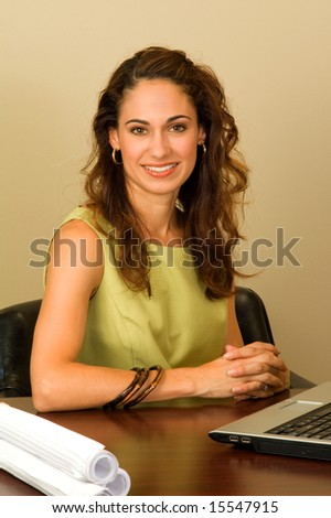 A pretty brunette business professional wearing a green outfit.