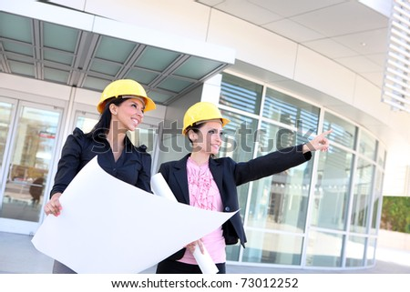 A pretty business woman construction team at office building with plans