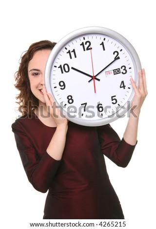 A pretty business woman hiding behind a clock
