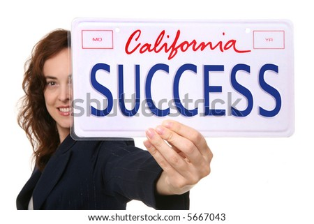 A pretty business woman holding a success license plate