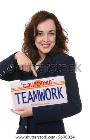A pretty business woman holding a teamwork license plate