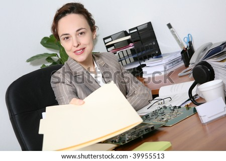 A pretty business woman in the office handing folders to boss