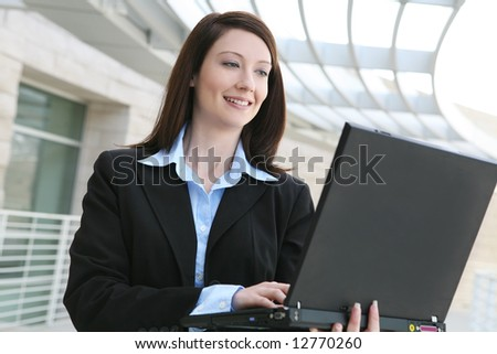 A pretty business woman on laptop computer  at office building