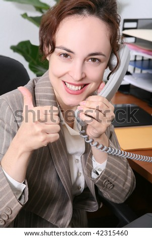 A pretty business woman on the phone celebrating a success - stock photo