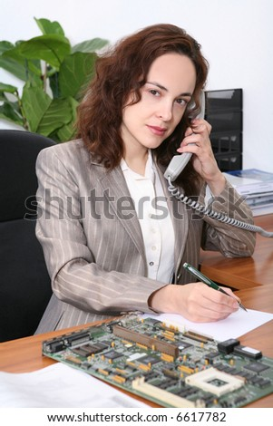 A pretty business woman on the phone with a printed circuit board