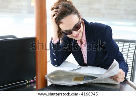A pretty business woman reading a newspaper