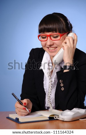A pretty business woman sitting at table and calling