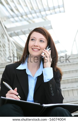 A pretty business woman sitting on the stairs on phone at company
