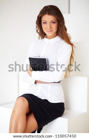A pretty business woman sitting on the stairs with notebook - stock photo