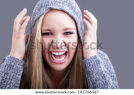 a pretty caucasian girl with blond hair wearing a hooded jersey raising her hands to her head and yelling in a sense of humor #143766487