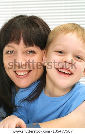 A pretty Caucasian mother and son a light background