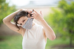 A pretty caucasian woman put on a fabric handmade mask on her face. Due to Covid-19 pandemic, it is recommended that everyone wear face covers while in public.