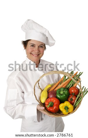 A pretty chef holding a basket of fresh vegetables.  Isolated on white.