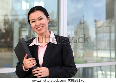 A pretty Chinese business woman smiling outside office building