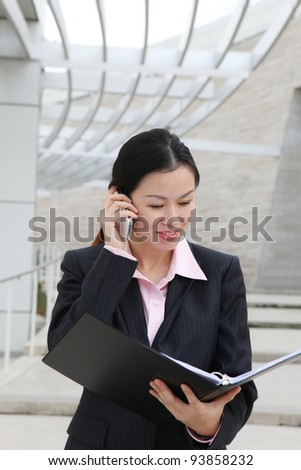 A pretty Chinese business woman smiling outside office building on phone