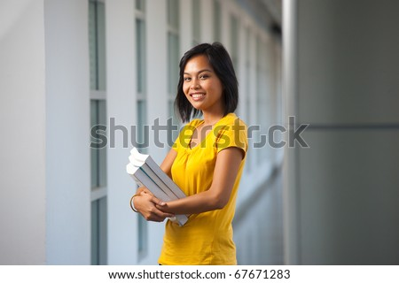 A pretty college student stands smiling with books in a modern hallway on a university campus.  Young female Asian Thai model late teens, early 20s of Chinese descent.