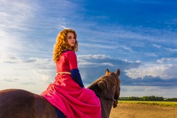 A pretty curly red haired attractive young Caucasian white woman looks at camera top down, riding a horse turns holding reins in sky clouds fields horizon. Horizontal day, summer outdoors copy-space