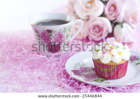 A pretty decorated cupcake with sprinkles and pink candy heart, with cup of coffee
