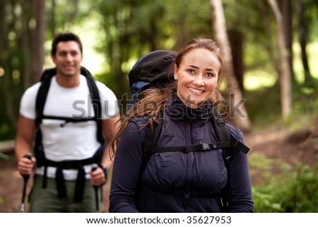 A pretty female on a camping trip with a male in the background