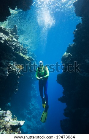 a pretty female scuba diver swimming between two coral cliffs, underwater