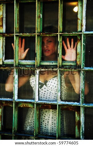 a pretty girl in a window of an old prison