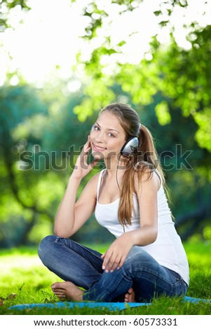 A pretty girl listens to music with headphones in the park