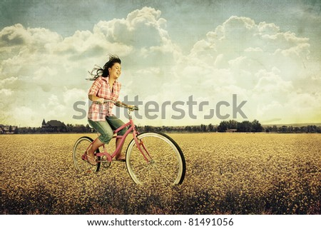 a pretty girl riding her bike in a field full of yellow flowers