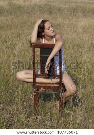 a pretty girl sleeping on a deck chair in the middle of a lawn during a sunny day. - stock photo