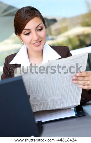 A Pretty Hispanic Business Woman with laptop computer reading newspaper