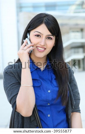 A pretty Indian business woman on the phone at office building