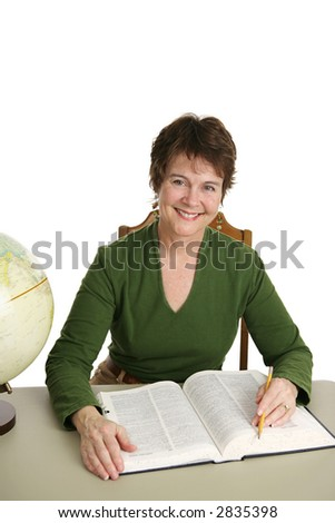 A pretty librarian at her desk doing research.  Isolated on white. - stock photo