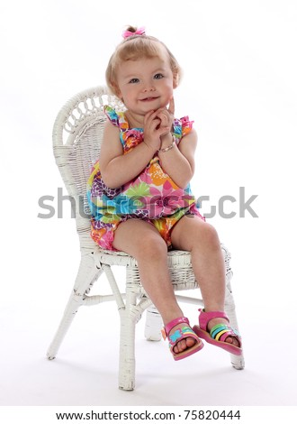 A Pretty Little Girl Sits Calmly in a Chair