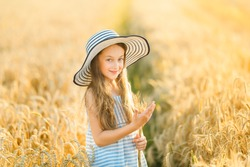 A pretty little girl stands in the middle of the field and holds a dry bunch of ripe golden rye. The child looks at the camera and smiles.