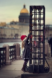A pretty little girl with a red hat and coat walking through the streets of St. Petersburg. Children in the city. Beautiful city.