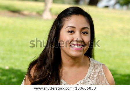 a pretty looking Hispanic woman smiling in the park.