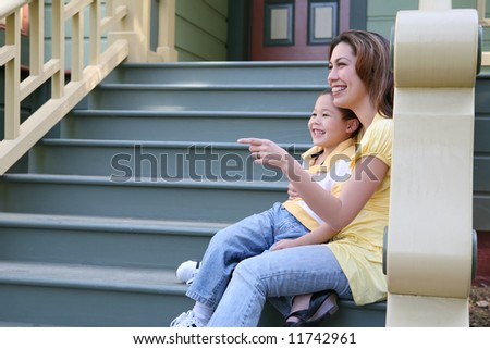 A pretty mother and cute son sitting on porch at home