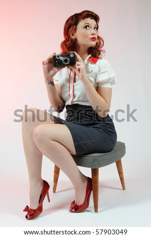A pretty pin-up girl with a vintage camera on a soft pink background.